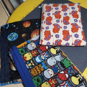 one completed zipper pouch, and the cut fabric stacks for two more, sitting on a pressing mat